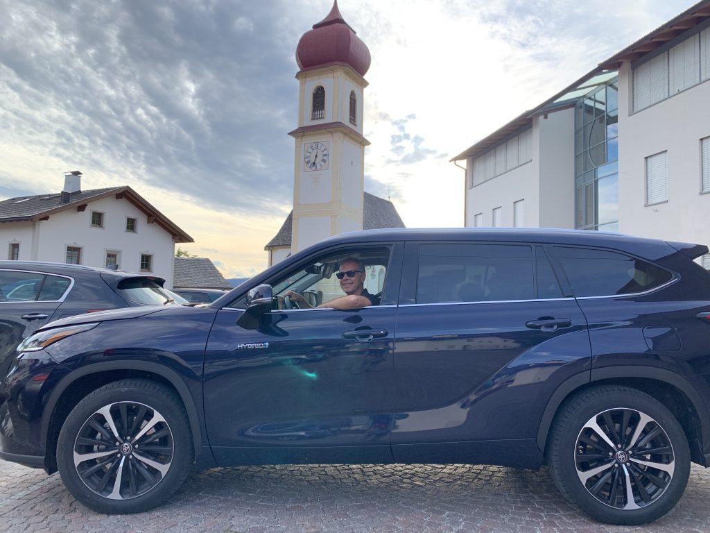 Fabio Orecchini al volante Toyota Highlander Hybrid con campanile Dolomiti San Pietro di Laion